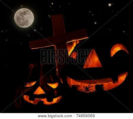 Scary glowing pumpkin decoration with creepy spider, burning fire, cross on the cemetery, Halloween fun, mysterious holiday celebration