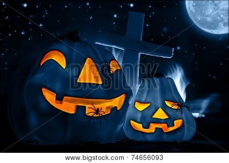 Scary glowing blue pumpkin decoration with creepy spiders, burning fire and cross on cemetery, Halloween celebration and fun of a creepy holiday