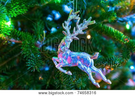Christmas ornament in the form of a stag hanging in a Christmas tree.