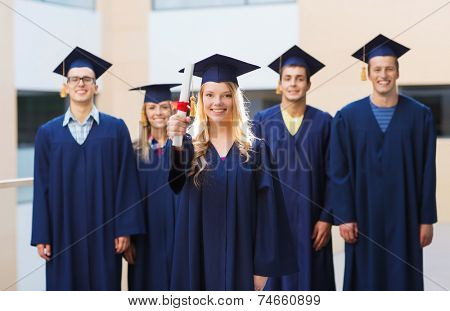 education, graduation and people concept - group of smiling students in mortarboards and gowns with diploma outdoors