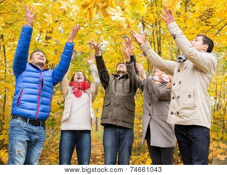 love, relationship, season, friendship and people concept - group of smiling men and women having fun in autumn park