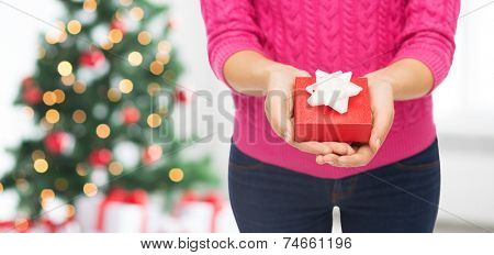 christmas, holidays and people concept - close up of woman in pink sweater holding gift box over living room and tree background