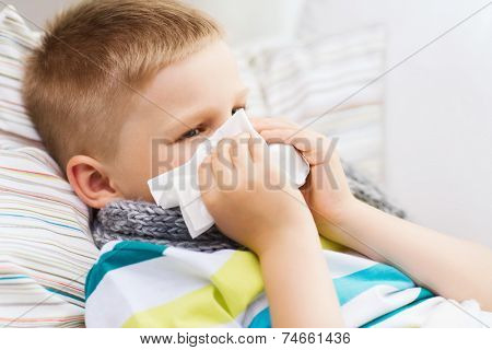 childhood, healthcare and medicine concept - ill boy with flu blowing nose at home