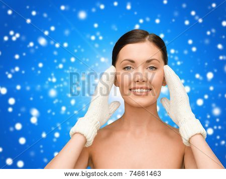 beauty, winter, people and health concept - smiling young woman in white mittens over blue snowy background