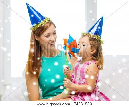 family, childhood, holidays and people concept - happy mother and daughter in blue party hats with pinwheel toy