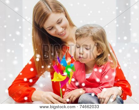 family, childhood, holidays and people concept - happy mother and daughter with pinwheel toy