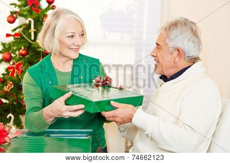 Two happy senior citizens celebrating christmas with gifts