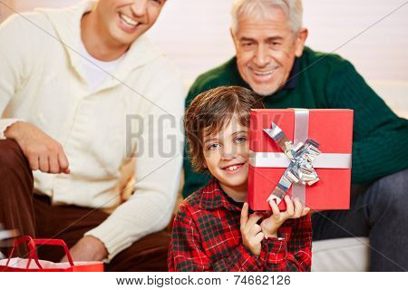 Happy boy showing red gift at christmas with dad and granddad watching