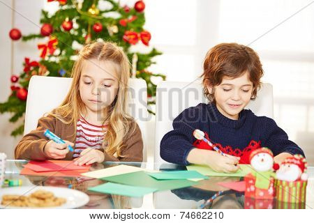 Two siblings drawing cards at christmas with handicrafts