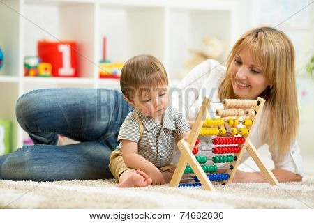 kid and mother playing with abacus