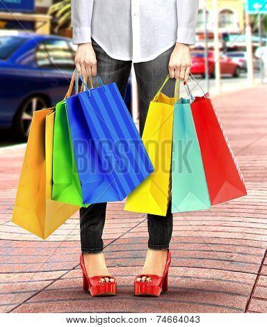 Women With Shopping Bags Walking on Sidewalk