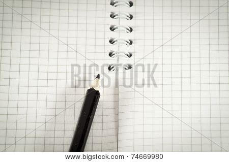 Black Pencil On A Background Of The Disclosed Notepad.