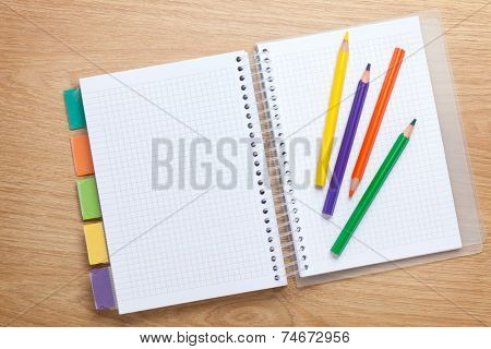Office table with blank notepad and colorful pencils. View from above with copy space