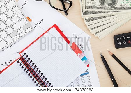 Office table with pc, supplies and money cash. View from above with notepad for copy space