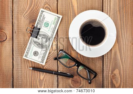 Money cash, glasses, pen and coffee cup on wooden table