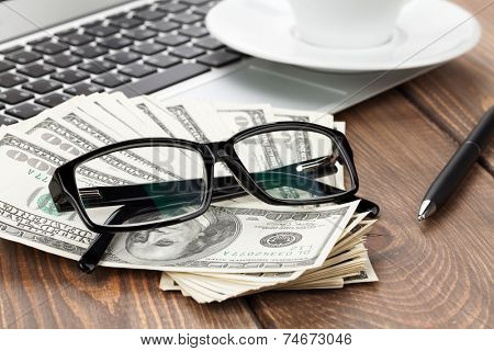 Office table with pc, coffee cup and glasses over money cash closeup