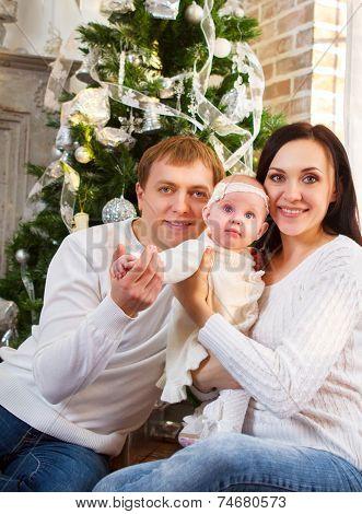 Happy Family With Christmas Baby Near The Christmas Tree