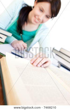Alegre estudante fazendo sua lição de casa sobre uma mesa