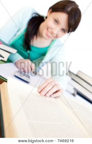 Positive Student Doing Her Homework On A Desk
