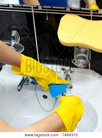 Close-up Of A Woman Cleaning A Bathroom's Sink