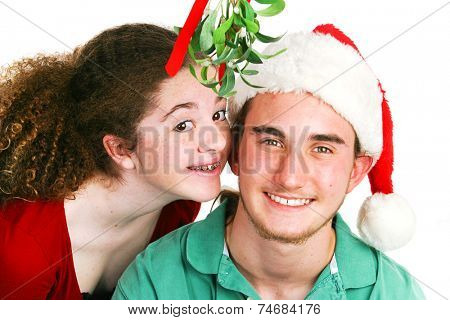 Cute teenage Latina girl ready to kiss her boyfriend under the mistletoe.  White background.  Christmas theme.