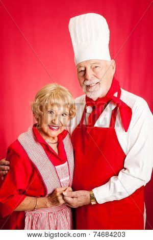 Portrait of a senior couple dressed to cook together.