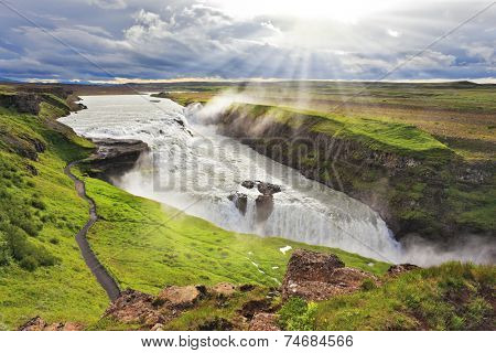 Roaring water glistens on the northern sun. Fantastically spectacular cascading waterfall Gyullfoss. Iceland in the summer
