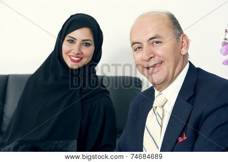 Business Meeting Between a Senior Businessman & a Woman wearing Hijab