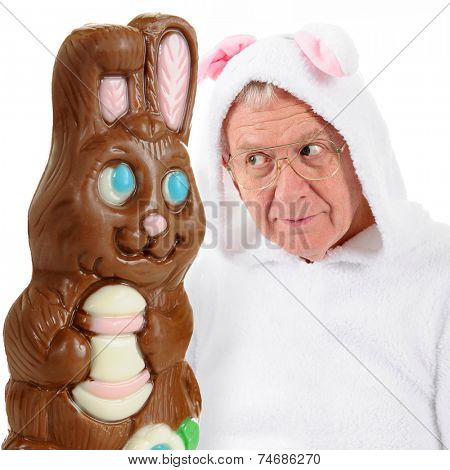 A giant chocolate bunny and a senior-man bunny eying each other as if vying for top spot on the Easter bunny scene.  On a white background.