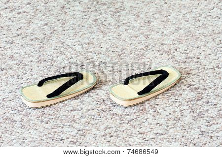 Pair Of Traditional Japanese Sandals On Carpet Floor.