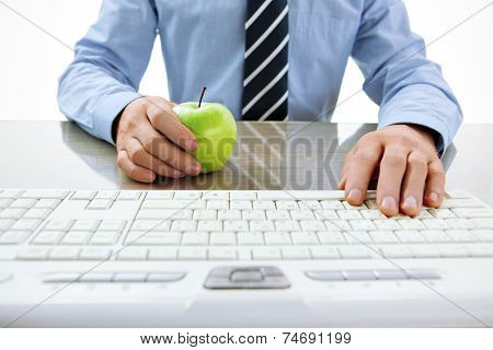 One hand typing text on keyboard and the other hand holding an apple. Healthy snacking concept