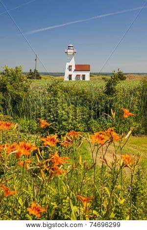 New London Range Rear Lighthouse with orange lilies in Queens County, Prince Edward Island, Canada.