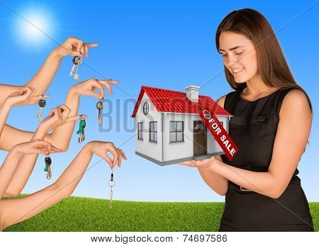 Beautiful girl holding house with label. Many hands are given keys