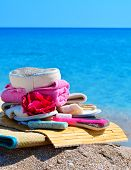picture of pumice-stone  - Natural bath sponges bath slippers pumice and towel against blue ocean - JPG