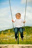 foto of swingset  - Little blonde boy having fun at the playground. Child playing on a swing outdoor. Happy active childhood.