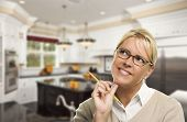 stock photo of daydreaming  - Attractive Daydreaming Woman with Pencil Inside Beautiful Custom Kitchen - JPG