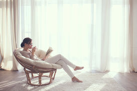 picture of in front  - Young woman at home sitting on modern chair in front of window relaxing in her living room reading book and drinking coffee or tea - JPG