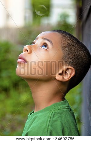 A boy looking at a bubble