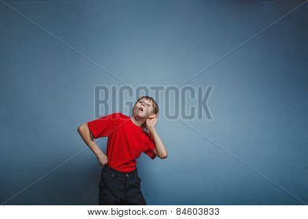 Boy, teenager, twelve years in a red shirt holding his ear hand,