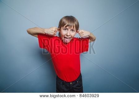 Boy, teenager, twelve years in the red shirt, pulled ears,