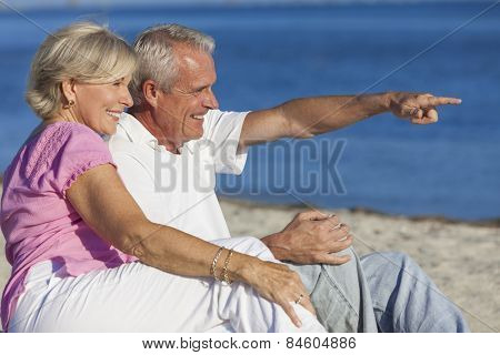 Senior man and woman couple sitting on a deserted beach pointing to the sea