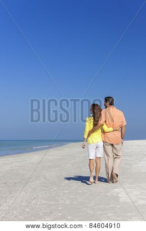 Rear view of man and woman romantic couple walking on a deserted tropical beach with bright clear blue sky