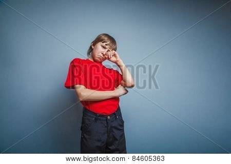 Boy, teenager, twelve years red in T-shirt, hand wipes tears, sa