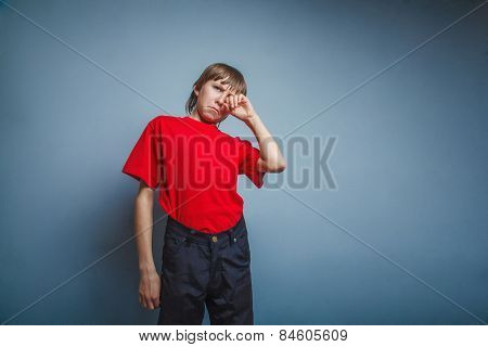 Boy, teenager, twelve years in  red T-shirt, hand wipes tears, s