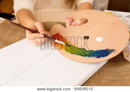 Closeup Shot Of Female Artist Mixing Oil Paints On Wooden Pallet