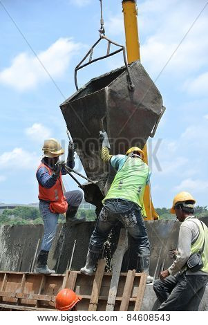 Group of construction workers casting concrete retaining wall