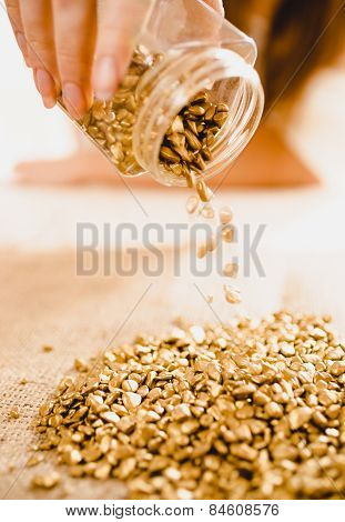 Conceptual Shot Of Hand Turning Over Bullion With Golden Nuggets
