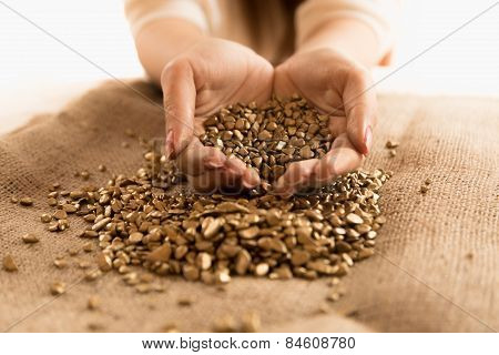 Closeup Shot Of Woman Holding Mound Of Golden Nuggets In Hands