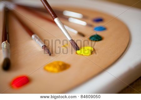 Paints On Wooden Pallet. Focus On Paintbrush Dipped In Yellow Paint