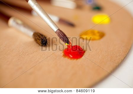 Professional Paintbrush Dipped In Red Oil Paint On Palette